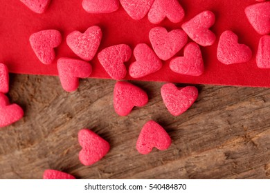 Small candy hearts on wooden table