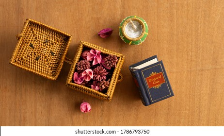 A small cane box with dry petals and mini Hindu holy book on wooden surface