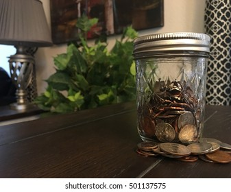 Small canning jar filled with spare change and coins pilled at base on table in room.