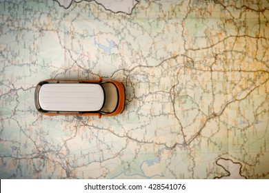 Small car on blurred map background,Image of travel concept,Top view.
