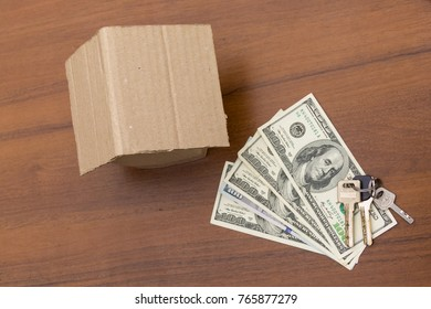 Small cardboard house, keys and dollars on wooden table. Credit, mortgage on living space. Purchase of housing. Real estate insurance. Rent of a dwelling