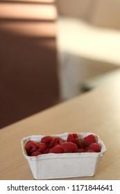 Small cardboard packae of raspberries. Selective focus, natural light.