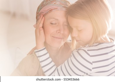 Small caring child embracing mother suffering from leukemia