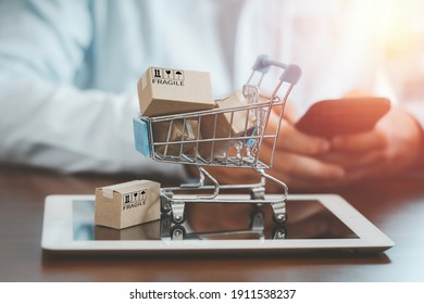 Small Cartons box with shopping trolley on tablet and shopper use smartphone to input order for online shopping concept.