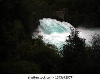 Small cascade waterfall in north island of New Zealand with very clean blue water and silhouetted bushes and shrubs surrounded