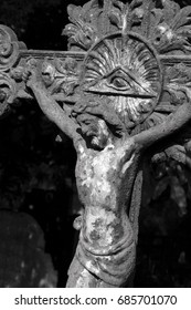 Small casted metal  statue of crucified Jesus Christ on cross with an Eye of Providence ( all seeing eye of God ) at the old cemetery in Serbia, detail in black and white