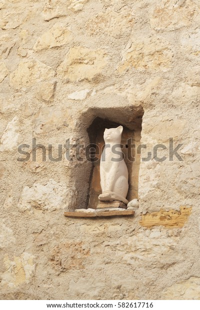 small cat sculpture in the street wall