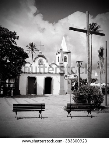 Small Catholic church with sign Praça Sao Francisco (San Francisco Square in Portuguese), Praia do Forte, Salvador, Bahia, Brazil. Black and white. Wooden cross and wooden benches in front of church.