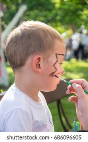 a small caucasian boy during face painting