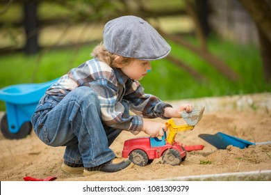 Small caucasian boy playing in sandpit. Handsome blonde 4 years boy in his sandbox.