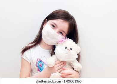 Small caucasian girl hugging teddy bear with smiling face or expression. Little kid and her toy with medical face mask. Coronavirus quarantine. Stop virus outbreak and protect loved ones concept.