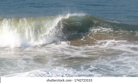 A small cean wave breaking and stirring up sand.