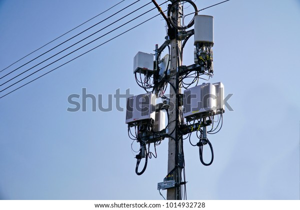 Small Cell 3G, 4G, 5G System. Macro Base Station or Base Transceiver Station on Electricity post. Wireless Communication Antenna Transmitter. Development of communication system in urban area.