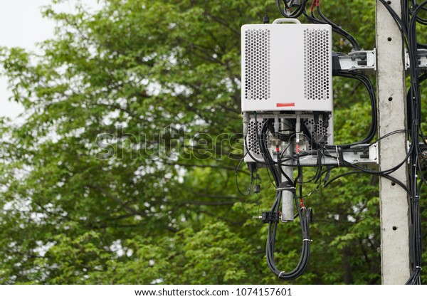 Small cellular 3G, 4G, 5G. Micro Base Station or Base Transceiver Station on Electricity post. Development of communication system in urban area with green environment.