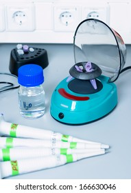 Small centrifuge and automatic pipettes in modern laboratory