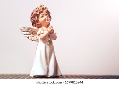 a small ceramic figure of a guardian angel clasping his hands in prayer. close-up, copyscape.