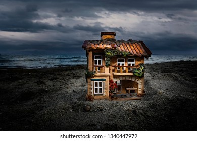 Small ceramic house on a beach a stormy day