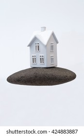 A small ceramic house on a strong foundation of a large rock. Great for concepts about foundations, home purchasing, insurance, or other abstract ideas. Vertical with copy space.