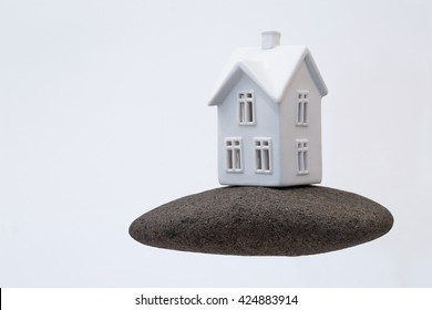 A small ceramic house on a strong foundation of a large rock. Great for concepts about foundations, home purchasing, insurance, or other abstract ideas. Horizontal with copy space.