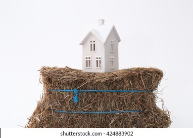 A small ceramic house on a weak foundation of a bale of hay. Great for concepts about foundations, home purchasing, insurance, or other abstract ideas. Horizontal with copy space.