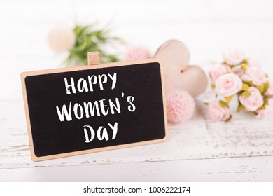 Small chalkboard for Women's day. Background with pink roses on old wooden table.