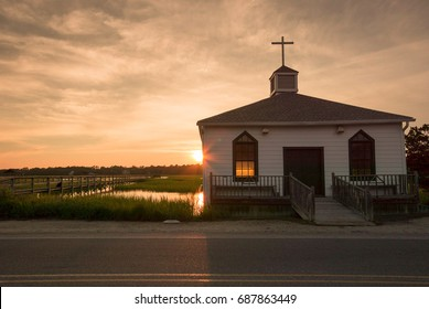 small chapel on the water with an illuminated window and a beautiful sunset on the South Carolina coast