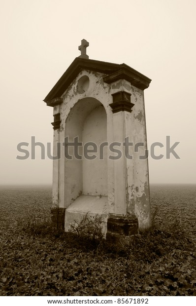 Small chapel standing lonely in fields in foggy weather. Sepia toned photograph.