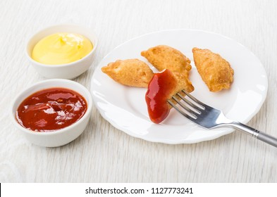 Small cheburek with ketchup strung on fork in plate, bowls with sauces on wooden table