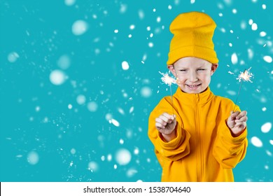 a small cheerful child in a yellow hat and jacket holds burning sparklers in his hands on a blue background