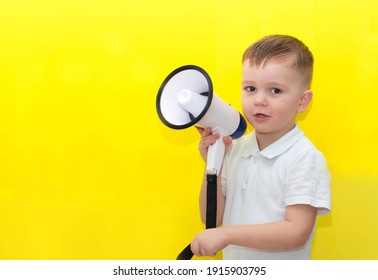Small cheerful toddler boy of 3-4 years old in white clothes holds in his hands; speaking into an electronic megaphone; isolated on an orange wall background; children's studio portrait.