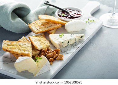 Small cheeseboard with brie, blue cheese, baguette and jam