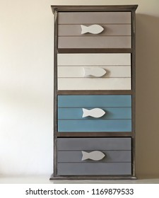 Small chest of drawers with fish shaped handles and four drawers of different and soft colors