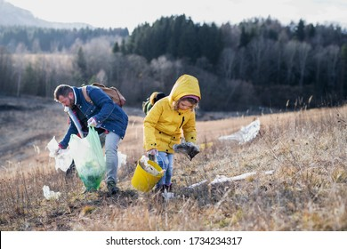 Small child with activists picking up litter in nature, environmental pollution concept.