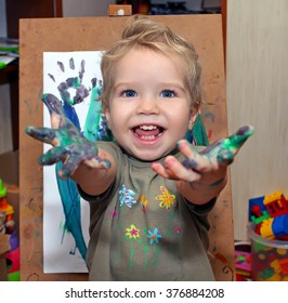 Small child with blue eyes, drawing finger paints. Babe shows palms soiled in a paint. Little painter with an easel painting the grass.