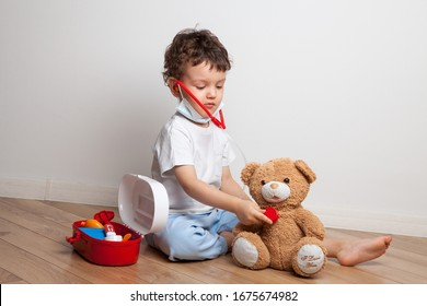 small child, a boy plays a doctor with a stethoscope on his neck and in a medical mask. listening to a teddy bear. fun activities for children and quarantine at home. learning in a playful way.