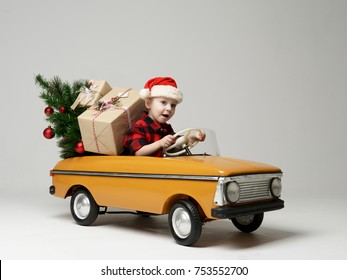 Small child boy in winter sitting in a yellow  retro toy car pulls on Christmas tree decorated on grey background