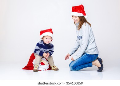 a small child in a Christmas hat and mother. Christmas and new year