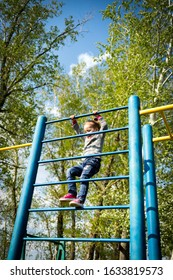 A small child climbs the swedish wall outdoors