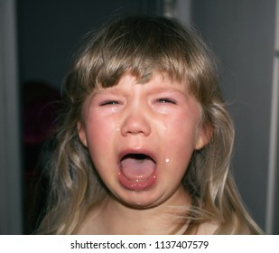 A small child is crying with tears and drooling. Children's hysteria.