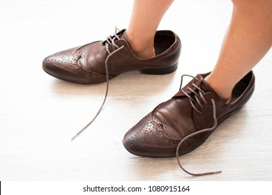 small child, dressed in brown shoes large adult. the child wore dad's shoes
