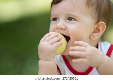 small child eats an apple in the summer and spring in nature