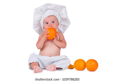A small child eats an orange slice in a chef suit on a white background.