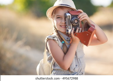 small child girl holding camera and taking photo of sunset landscape, standing on hill with background of mountains and sea, traveling photographer. girl with backpack, suitcase, summer hat