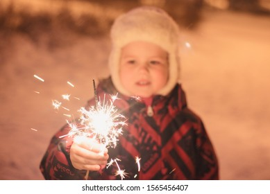 small child, girl holding a Sparkler, looking at the fire, romantic look, can be used as a background