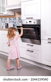 small child girl opens door of hot oven in a white country style kitchen. she is unattended in a dangerous situation. she wears a violet dress and shoes.