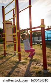 A small child goes in for sports in the stadium. hanging on the horizontal bar, on the uneven bars