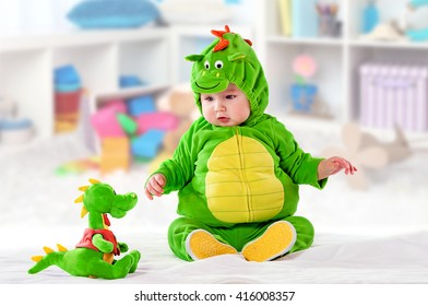 the small child in a green suit of a dragon