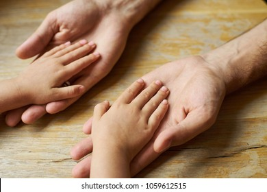 Small child hands in big parent hands close up