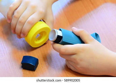 Small child holding asthma inhaler and spacer in his hands. Medication and medical devices for treatment and management bronchial asthma, allergy. How to use an aerosol inhaler with a spacer