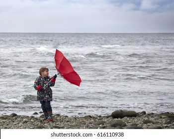 Small child holding his inside out umbrella on a windy day at the beach.